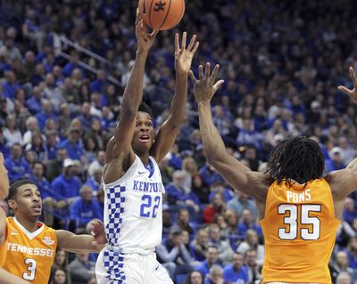Kentucky's Shai Gilgeous-Alexander (22) passes away from the defense of Tennessee's James Daniel III (3) and Yves Pons (35) during the first half of an NCAA college basketball game, Tuesday, Feb. 6, 2018, in Lexington, Ky. (James Crisp / Associated Press)