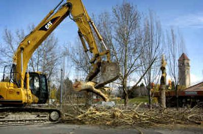 A pair of trees are cleared Thursday morning to make room for the Rotary fountain in Riverfront Park, a $1.5-million project next to the Carousel. The Carousel concessions building also was demolished.   (Holly Pickett / The Spokesman-Review)