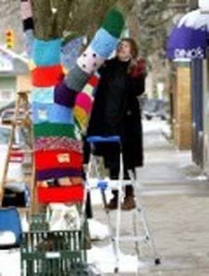 "Corrine Bayraktaroglu adds another section of knitting to  the ""Knit Knot Tree"" on Xenia Ave. in Yellow Springs, Ohio on Wednesday, Feb. 27, 2008. The art project in this southwest Ohio village, already known for its artistic flavor and offbeat art, has become a conversation piece and even a photo op. (AP Photo/Skip Peterson) ORG XMIT: OHSP101 (Skip Peterson / The Spokesman-Review)"