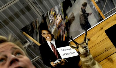 Nathaniel Pulliam of Black Sheep Sporting Goods works the gun counter on Wednesday. The owners put up the cutout of Barack Obama after the election.  (Kathy Plonka / The Spokesman-Review)