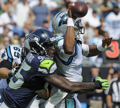 Carolina Panthers quarterback Cam Newton (1) is hit as he throws a pass by Seattle Seahawks' Benson Mayowa (95) during the second half of an NFL football game in Charlotte, N.C., Sunday, Sept. 8, 2013. (Mike McCarn / Associated Press)