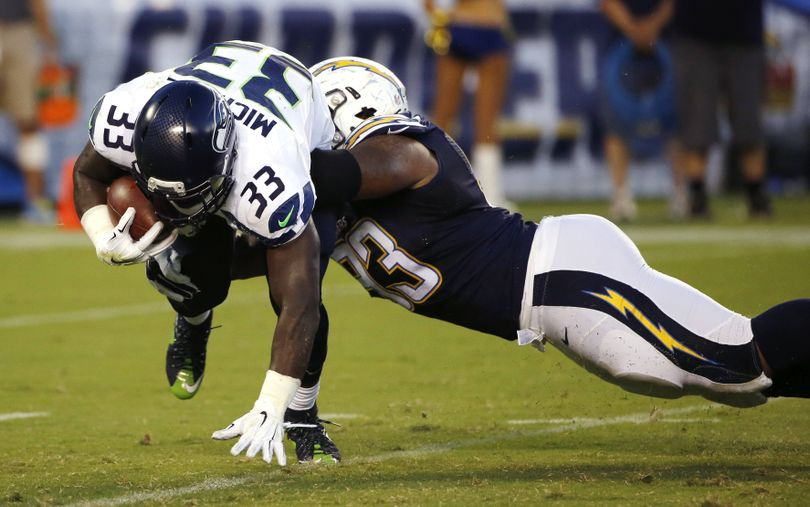 Seahawks running back Christine Michael is brought down by Darius Philon. (Associated Press)