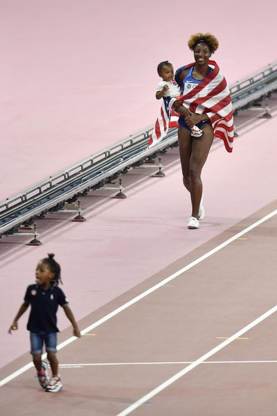 Nia Ali, of the United States, celebrates with her baby after winning the the women's 100 meter hurdles at the World Athletics Championships in Doha, Qatar, Sunday, Oct. 6, 2019. (Martin Meissner / Associated Press)