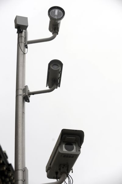 The red light camera system in Spokane uses two cameras and a flash on a pole, plus a control box, which combine to monitor the roadway for red light runners. (File)