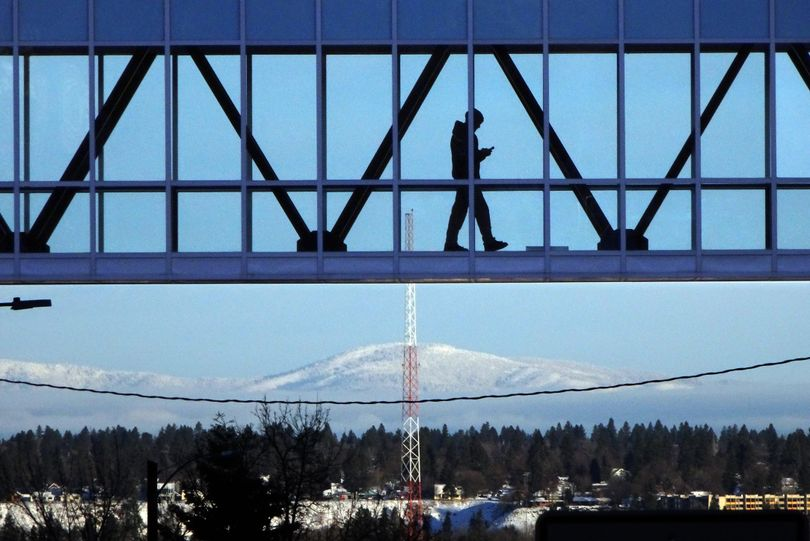 A pedestrian walks across the sky bridge Wednesday, Dec. 28, 2016, between the Providence Medical Center building and the Doctors Building on the South Hill, as the snowy hills of north Spokane appear in the background. (Jesse Tinsley / The Spokesman-Review)
