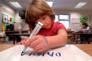 Dakota Taylor, a kindergartener at Fernan Elementary, writes her name on her whiteboard during class Wednesday. She is one of a growing number of Coeur d'Alene children taking part in extended-day kindergarten.   (Jesse Tinsley / The Spokesman-Review)