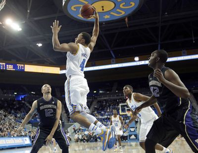 UCLA's Norman Powell, who scored game-high 24 points, goes up for a dunk as UW's Quevyn Winters, left, and Donaven Dorsey look on. (Associated Press)