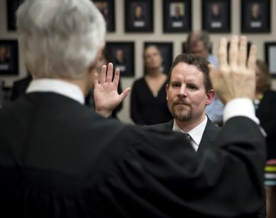 FILE – Superior Court Judge Michael Price (back to camera) swears in new Spokane County Superior Court Judge Tony Hazel during an investiture held Friday, May 5, 2017, at the Gonzaga University Law School. (Colin Mulvany / The Spokesman-Review)