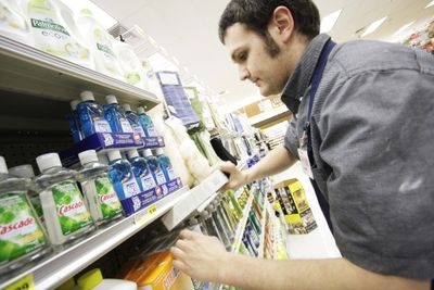 Employee Jesse McCauley stocks  phosphate-free dishwashing machine detergent at a Rosauers supermarket in Spokane on Tuesday.  (Associated Press / The Spokesman-Review)