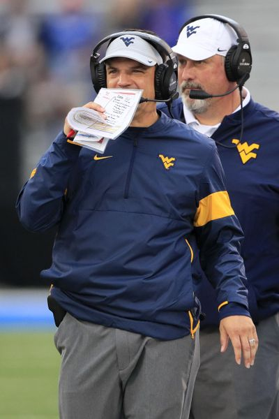 West Virginia head coach Neal Brown covers his mouth while talking on his headset during the second half of an NCAA college football game against Kansas in Lawrence, Kan., Saturday, Sept. 21, 2019. West Virginia defeated Kansas 29-24. (Orlin Wagner / Associated Press)