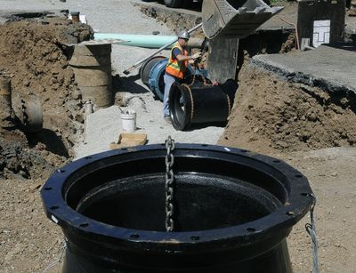 Brent Imholt, of the Spokane Water Department construction crew, attaches a chain to a 30-inch water main tee on Friday. Crews are working at the corner of 37th Avenue and Stone Street on a three-month project to replace the old pipes, which waste water through leaks.  (Dan Pelle / The Spokesman-Review)