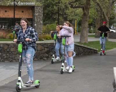 Teens ride Lime scooters around Riverfront Park on Friday. The scooters are a popular way for teens to pass the time in the park with their friends.  (Jesse Tinsley/THE SPOKESMAN-REVIEW)