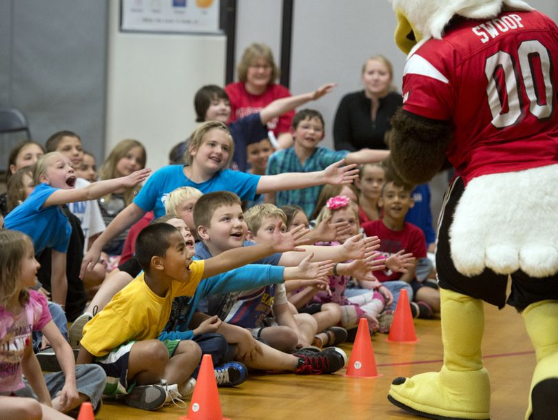 Broadway Elementary School students extend hands for high-fives from from Swoop, the Eastern Washington University mascot during an assembly, May 17 in the school gym. (Dan Pelle)