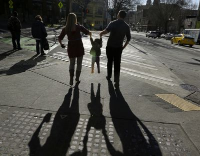 A child is lifted by her parents at a street corner in downtown Seattle in this file photo.  (Ted S. Warren)