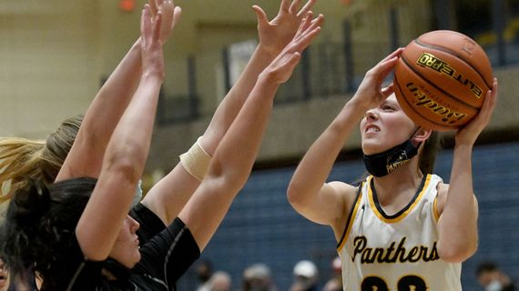 Mead's Olivia Moore takes a shot over a pair of University defenders during a GSL game at Mead High School on Friday, May 28, 2021.  (Kathy Plonka/The Spokesman-Review)