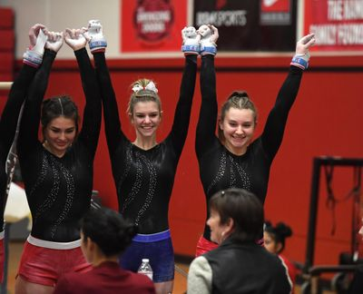 Mead gymnast Lexi Weller, right, and teammates address the judges before competing on the balance beam on Dec. 13, 2018, at North Central High. (Dan Pelle / The Spokesman-Review)
