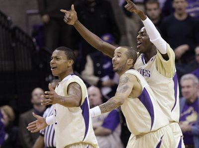 UW's Isaiah Thomas, left, Venoy Overton and Justin Holiday celebrate during their victory over UCLA on Saturday. (Associated Press / The Spokesman-Review)