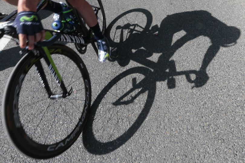 A cyclist casts a shadow on the tarmac prior to the start of the eleventh stage of the Tour de France cycling race over 116.8 miles with start in Pau and finish in Cauterets, France, Wednesday, July 15, 2015.  (AP Photo/Christophe Ena)