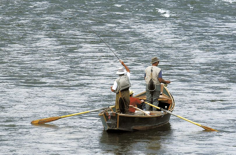 FILE - In this Sept. 9, 2004, file photo, two fly fishermen and an oarsman test their angling skills as they float down the Yellowstone River near Pine Creek, Mont., fishing access. Montana is closing a  183-mile stretch of the Yellowstone River to all recreational activities to prevent the spread of a parasite that is believed to have killed tens of thousands of fish, authorities said Friday. (Garrett Cheen / Associated Press)