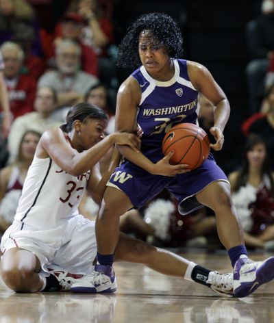Washington's Jazmine Davis takes Stanford's Amber Orrange for a ride during second-half action Saturday. (Associated Press)