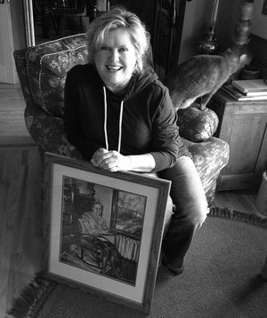 Spokane artist Gina Freuen with an early painting by her mother. (cheryl-Anne Millsap / Photo by Cheryl-Anne Millsap)