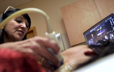Terri  Porcarelli, a registered diagnostic medical sonographer, works with a patient on  April 22 at Inside View Health Screening.  (Kathy Plonka / The Spokesman-Review)