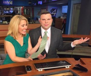 Chief meteorologist Kris Crocker has fun with KXLY colleague Casey Lund's S&H Green Stamps tie on St. Patrick's Day last Friday. (Photo courtesy of KXLY News)