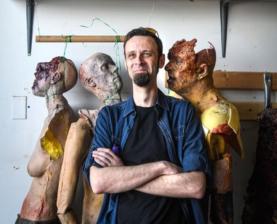 Z Nation actor Matt Davidson stands with rubber foam body of his likeness (second face from left, bottom row). The Z Nation team is liquidating a warehouse full of costumes and props used on the show. (Dan Pelle / The Spokesman-Review)