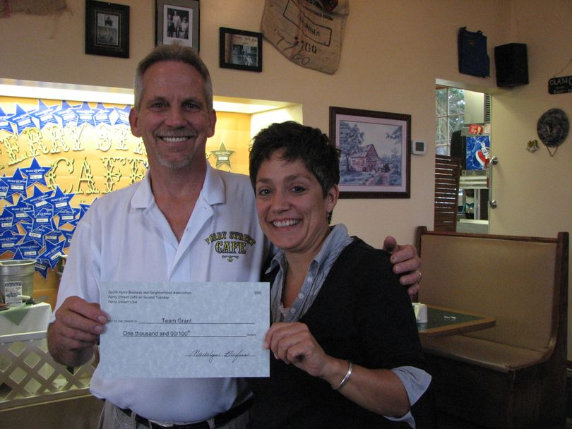 South Perry Cafe owner Geoff White and Grant Elementary teacher Kris Gladeau hold the $1,000 check that was donated to Grant Elementary's library program from the proceeds of the 2010 South Perry Fair and Parade. (Pia Hallenberg)