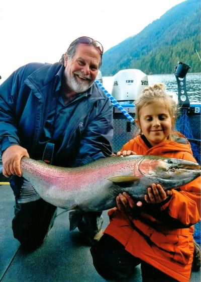 "Sophie Egizi, 8, of Sandpoint, poses with her catch-and-release record-breaking Gerrard rainbow trout on Oct. 11, 2019. Egizi, who's joined by Capt. Bob Wiley of Pend Oreille Charters, named the fish ""Old Man Sparkles."" (Bob Egizi / COURTESY)"