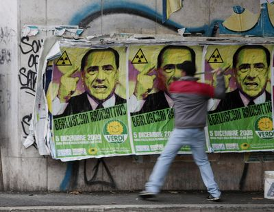 """A man spreads glue over Green Party posters showing pictures of Italian Prime Minister Silvio Berlusconi and promoting a """"No B Day"""" protest – with the """"B"""" standing for Berlusconi – in Rome on Monday.  (Associated Press)"""