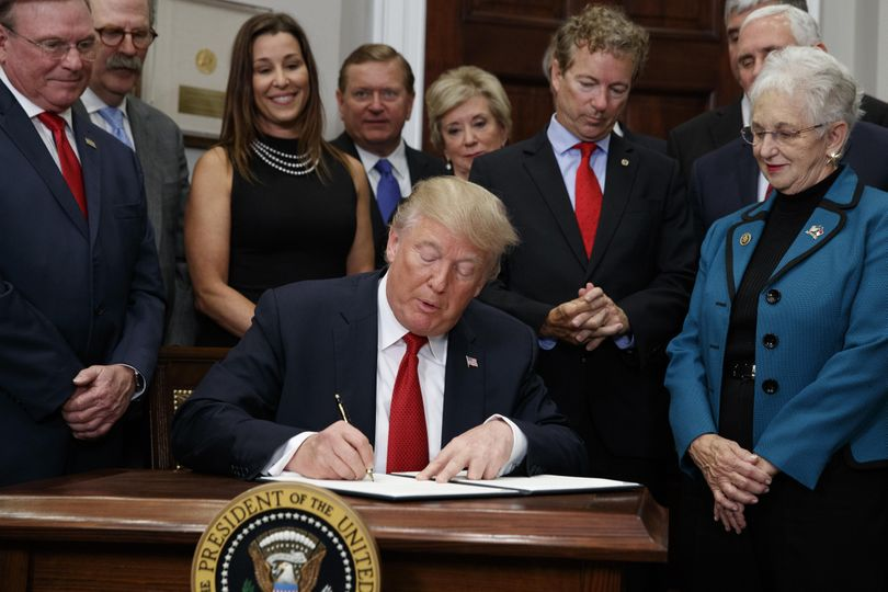 President Donald Trump signs an executive order on health care in the Roosevelt Room of the White House on Thursday in Washington, D.C. (Evan Vucci / Associated Press)