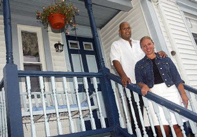 Beth Gissinger and Luis Rivera stand on the back porch of their house in Fairhaven, Mass. Smaller cities and towns are luring away urban professionals seeking a better life.  (Associated Press / The Spokesman-Review)