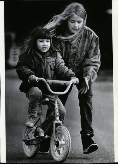A steadying hand from her big sister Angie, 11, helps 4-year-old Tristan Umland learn to ride a bike without training wheels Thursday, March 30, 1989, in Post Falls. Cindy Hval says time seemed endless in childhood for riding her bike and her favorate pastime – reading. (Anne C. Williams / The Spokesman-Review archive)