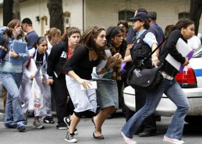 Students run from Dawson College in Montreal, Canada, on Wednesday after reports of a gunman in the building. At least 20 people were wounded before the gunman was killed; one later died.  (Associated Press photos / The Spokesman-Review)