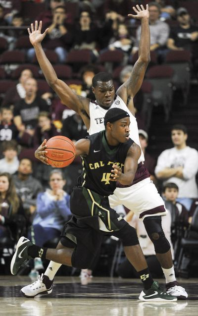 Cal Poly guard Jaylen Shead  dribbles around Texas A&M guard Jalen Jones during the second half on Tuesday, Dec. 29, 2015, in College Station, Texas. (Eric Christian Smith / AP)