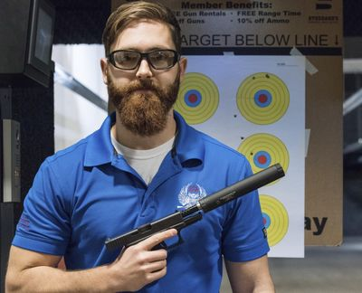 """FILE - In this photo taken Jan. 27, 2017, Knox Williams, president and executive director of the Georgia-based American Suppressor Association, poses for a portrait while holding a handgun with a """"silencer,"""" in Atlanta. Rep. Cathy McMorris Rodgers said she needed to """"take another look at"""" a law that would ease some of the restrictions on civilians buying the devices. (Lisa Marie Pane / AP)"""