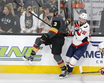 Washington Capitals center Evgeny Kuznetsov, right, winces as he is checked by Vegas Golden Knights defenseman Brayden McNabb during the first period in Game 2 of the  Stanley Cup Finals on Wednesday in Las Vegas. (Ross D. Franklin / Associated Press)