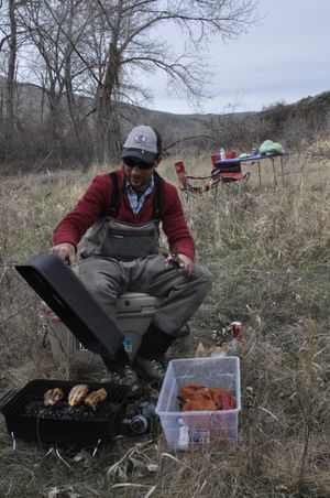 Yakima River fly fishing guide Stefan Woodruff barbecues chicken for lunch along the Yakima River. (Rich Landers)