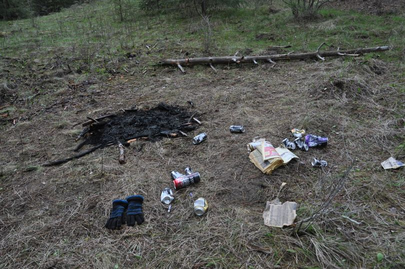 Alcoholic beverage cans, a ripped up phone book and other garbage along with an illegal fire mar a site that had just been cleaned up the previous weekend in the Dishman Hills Natural Area in April, 2011. (Rich Landers)