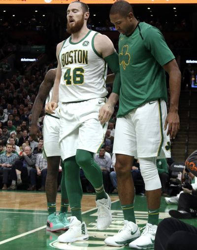 Boston Celtics center Aron Baynes, left, broke his hand in the first quarter of a 111-103 loss to the Phoenix Suns on Wednesday night in Boston. (Elise Amendola / AP)