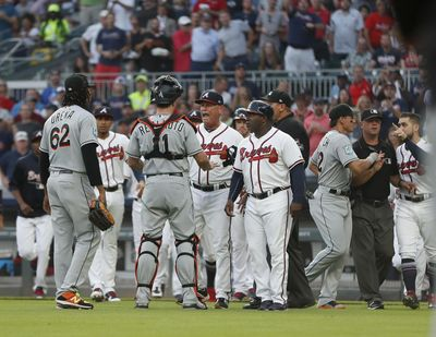 Marlins catcher J.T. Realmuto stands between pitcher Jose Urena, left, and Braves manager Brian Snitker after Urena hit Atlanta rookie Ronald Acuna Jr. with the first pitch of the game on Wednesday. (John Bazemore / AP)