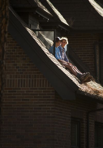 As a windstorm arrives, Whitworth University students Eli Deitz, 19, left, and Elisabeth Spencer, 20, watch pine needles fly from the window ledge of Deitz's McMillan Hall dorm room on Tuesday. (Colin Mulvany)