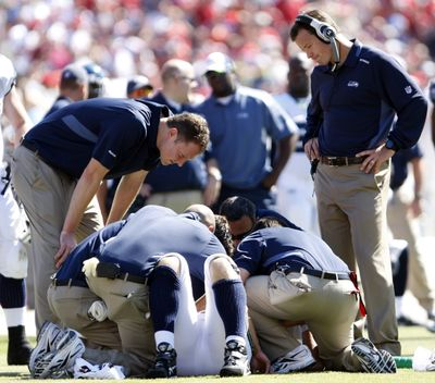 Coach Jim Mora, right, looks on last Sunday as Matt Hasselbeck is tended to. (Associated Press / The Spokesman-Review)