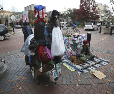 In a Nov. 10, 2016 photo, a visitor hauls a cart full of belongings through downtown Eugene, left, past another visitor asking for money at Broadway and Willamette in Eugene, Ore. A wave of complaints about aggressive dogs in the downtown area of Oregon's third most populous city has prompted Eugene city councilors to ban dogs from the downtown area except those owned by people who live or work there. (Chris Pietsch / AP)