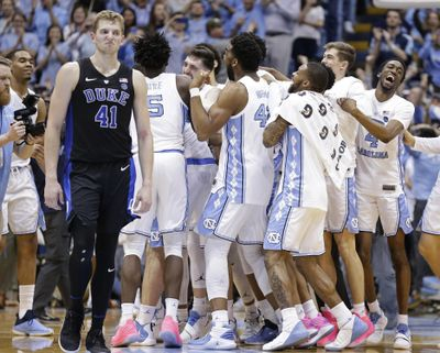 North Carolina players celebrate while Duke's Jack White (41) walks away following an NCAA college basketball game in Chapel Hill, N.C., Saturday, March 9, 2019. North Carolina won 79-70. (Gerry Broome / AP)