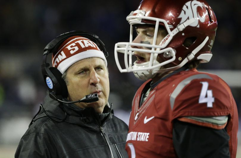 Washington State coach Mike Leach likes the personal approach to getting the ear of his players, as he did here last season with quarterback Luke Falk. (Associated Press)