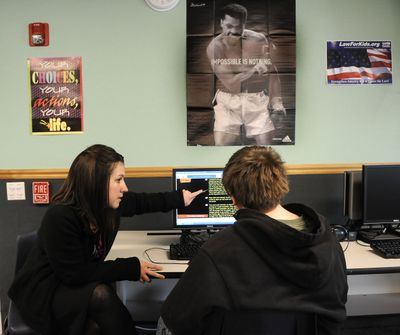 Paraeducator Tiah Scarlett works with East Valley Middle School student Brandon Armstrong on an online language arts assignment Wednesday in Otis Orchards. (Dan Pelle / The Spokesman-Review)
