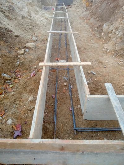 Those gray bumpy rods are ½-inch steel reinforcing bars that will strengthen a garage footing. The contractor now needs to put supports under them so about 3 or 4 inches of concrete separates the rods from the soil. Then it's time to pour concrete.  (Tim Carter)