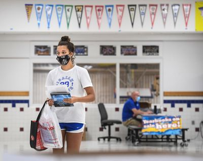 Chase Middle School eighth-grade student Kennedy Smith cleared out her locker and picked up her yearbook Thursday  (DAN PELLE/The Spokesman-Review)
